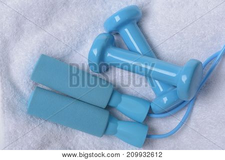 Dumbbells And Skipping Rope In Cyan Color On Soft Cloth