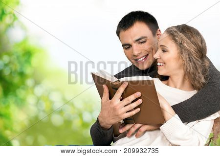 Young couple reading book young couple green background