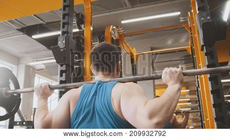 Fitness gym - muscular man performs squats with barbell - rear view, close up