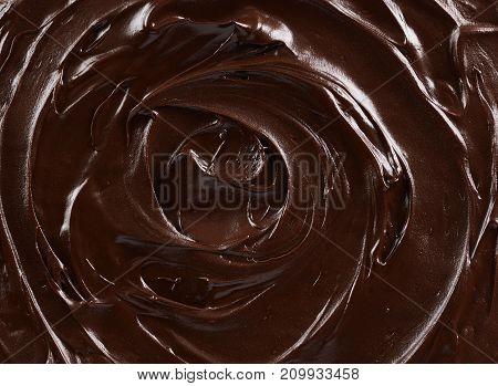 Texture of dark chocolate icing swirl close up. Food background macro