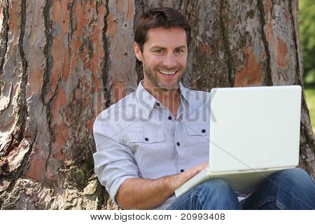 Smiling man using laptop computer in the park