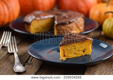 Delicious homemade pumpkin cake with chocolate icing served on dark blue plates with bright orange pumpkins closeup