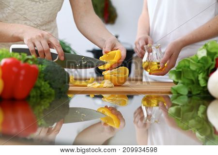 Close-up of  human hands  cooking in a kitchen. Friends having fun while preparing fresh salad. Vegetarian, healthy meal and friendship concept.