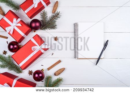 Top view of blank notebook on white wooden background with xmas decorations copy space. Christmas background with notebook for wish list or to do list red gift boxes fir tree branches. Flat lay
