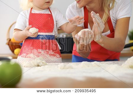 Mother and her cute daughter hands prepares the dough on wooden table. Homemade pastry for bread or pizza. Bakery background.