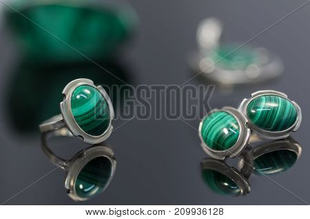 Closeup vintage silver earrings and ring with malachite on background of silver pendant and piece of malachite on black acrylic board. Selective focus.