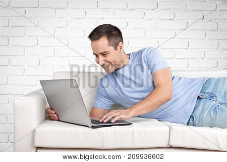 Man laptop sofa dining room computer happy person