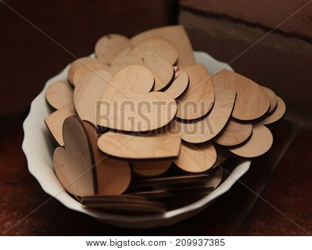 Carved Wooden Hearts On A White Plate.