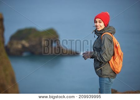 Girl in warm clothing, in red knitted hat and small orange backpack stands on the cliff on background of ocean, sky and Reynisfjara beach in Iceland. Popular tourist attraction. Unusual and gorgeous scene. Location Sudurland, cape Dyrholaey, coast of Icel