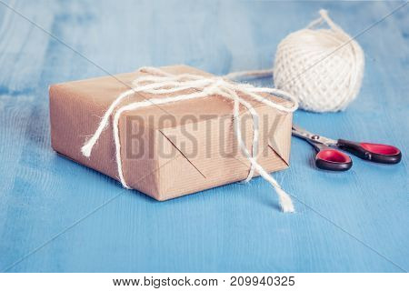 Paper wrapped gift - Homemade gift box wrapped with classic brown paper and tied with white string scissors and twine in background