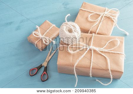 Stack of homemade gift boxes - High angle view image with homemade gift boxes of different sizes wrapped with classic brown paper on a wooden table.