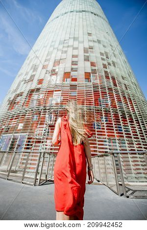 BARCELONA, SPAIN - August 17, 2017: Woman in red dress walking to the famous Agbar office tower, designed by French architect Jean Nouvel in Barcelona
