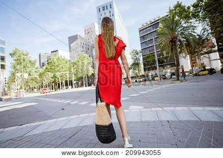 Woman in red dress walking back on the street at the financial district with beautiful scyscrapers in Barcelona