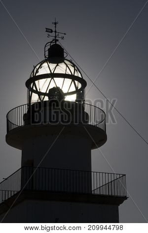 Lighthouse on sunset with the sun behind it. Costa Brava Spain