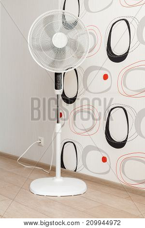 A white electric fan stands in a spacious room and cools the air