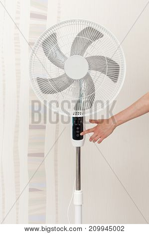 Hand presses the button on the control panel on the white electric fan Concept : Save Energy Save World Save money Selective focus.
