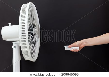 White electric fan turns on turns off with the remote control. Hand hold electric fan remote.