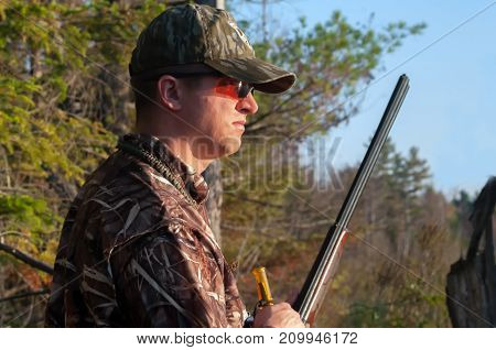 Hunter Preparing to Call Duck in the fall along a pond