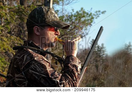 Hunter calling Ducks along a pond in the fall