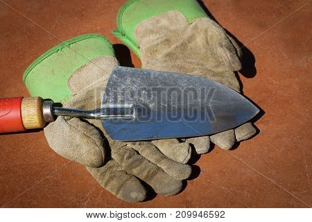 Silver metal garden trowel with red wooden handle resting on top of a pair of worn, dirty leather green and gray workmen's gloves, all on a brown table top after digging in a garden.
