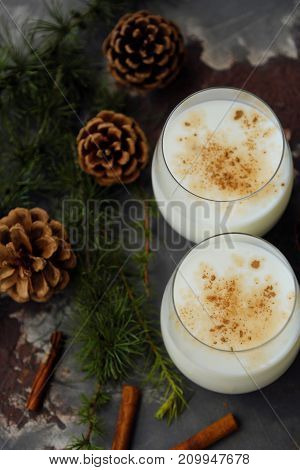 Delicious milkshake with cinnamon and pine on the table