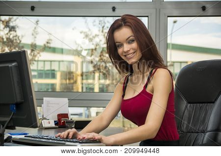 Pretty young woman working in office on computer at her desk, with a friendly attitude