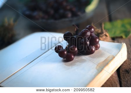 Autumn still life: Grapes with a book on a wooden background