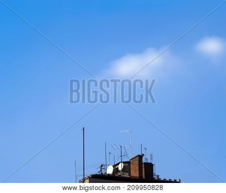 lots of television antennas on a blue sky background