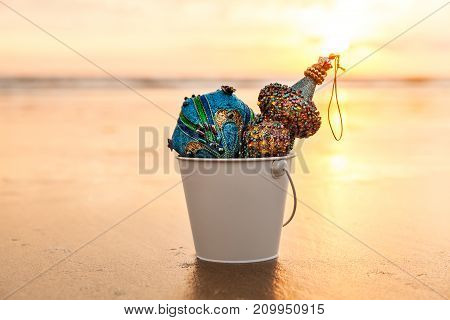 Blue Christmas Decorations collected in a white bucket at Golden Sunset on the background of Beach and Sea Winter Holiday Concept Horizontal Composition
