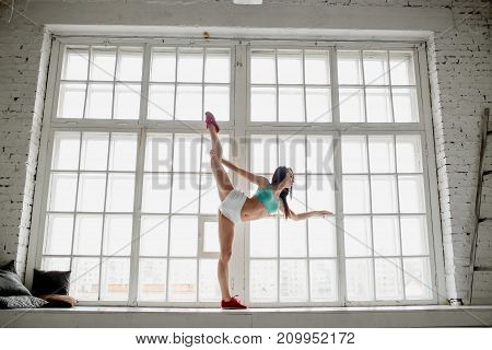Profile portrait of beautiful young woman in aquamarine top and white shorts standing split against big window. Full length. Concept yoga, Pilates, gymnastic.