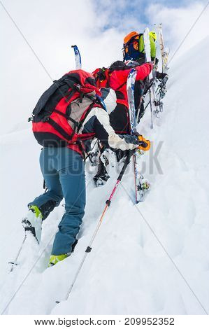 Skiiers climbing a steep slope. Back-country skiing in the mountains.