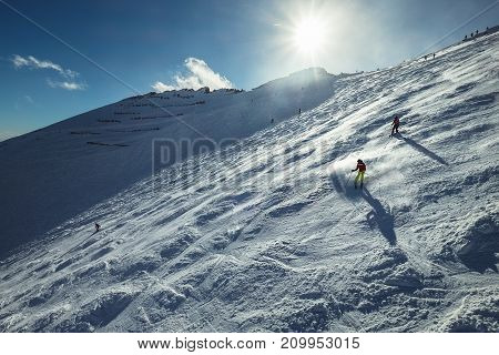 Skiers go down the snowy mountain hill