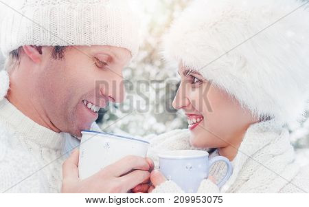 Cozy dressed couple drink hot tea on snow forest glade