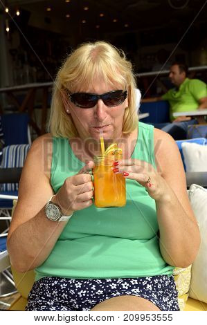 Paxos Corfu Greece - October 1 2017 : Lady drinking a glass of fresh orange in Paxos harbour