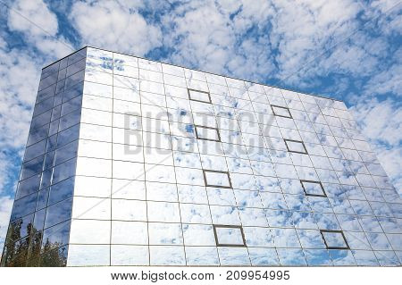 Modern building made of glass is stand on background of a blue cloudy sky. Left view