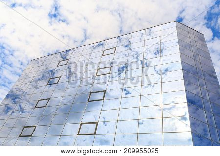 Blue clouds and sun are reflected in the glasses of windows of a modern building