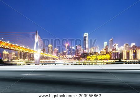 blurry view of empty asphalt road and suspension bridge and cityscape of chongqing at night