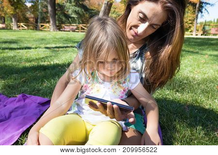 Little Girl And Mother Watching Mobile Sitting On Grass
