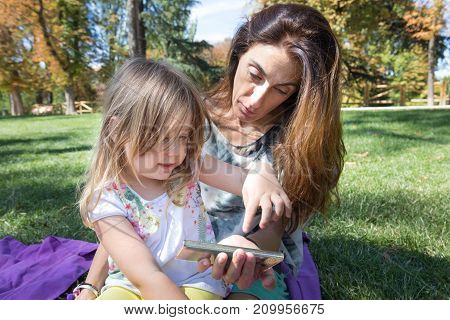 Little Girl Pointing With Finger Screen Of Smartphone Of Woman Sitting In Park