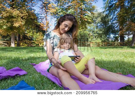 Little Girl Sitting On Mother Watching Mobile In Park