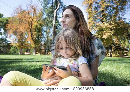 Little Girl Watching Mobile Sitting On Woman Legs In Park