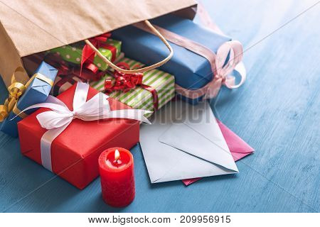 Shopping bag full of colorful presents paper wrapped and tied with ribbon and bows overturned on a blue wooden table over closed envelopes near a red candle.