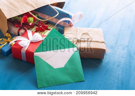 Green envelope with blank white paper leaning against a bunch of colorful presents that come out of a brown shopping bag on a blue wooden background.