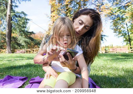 Woman And Little Girl With Surprise Face Watching Mobile Sitting In Park