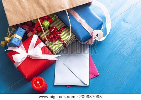 Brown paper bag overturned on a blue wooden table while multicolored presents and closed envelopes come out of it near a red lit candle.