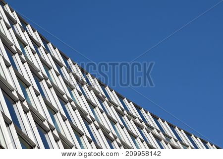 modern architecture window facade of the urban building in hamburg diagonal against the blue sky with copy space can be used as a background