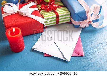 Multicolored presents wrapped in paper and tied with ribbon and bow displayed on a wooden table empty envelopes and a red lit candle.