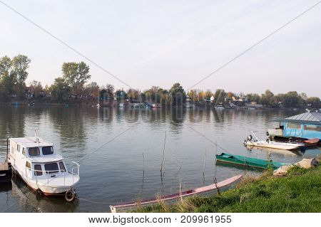 Look at the Tisa River from the riverside. A few boats on the river along the riverside.