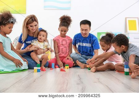 Young volunteers playing with little children in light room. Volunteering abroad concept