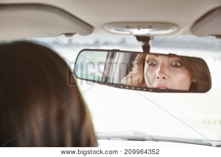 Reflection of woman in car rear view mirror